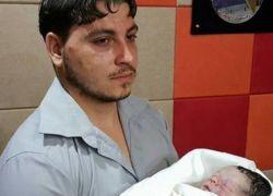 مواطن يحمل طفلته الميتة بين ذراعيه في مقر إذاعة محلية بغزة